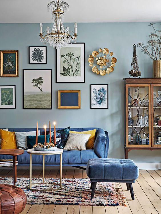 a vintage inspired blue living room with light walls, bold furniture, a gallery wall with various artworks and gold touches