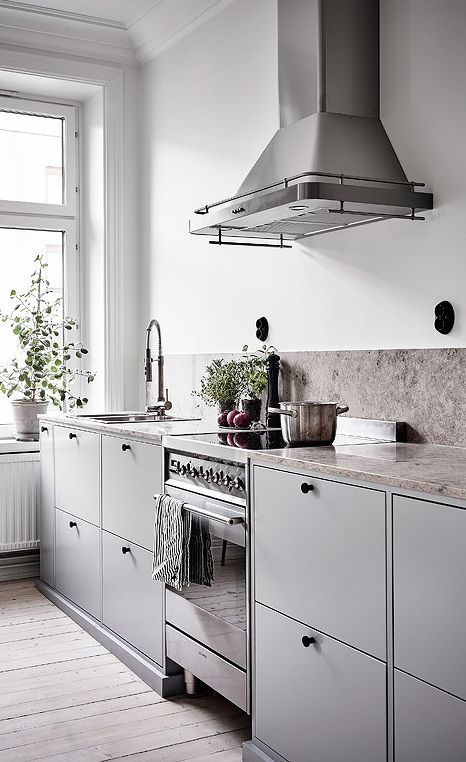 a Scandinavian grey kitchen with a greige stone backsplash and countertops, black fixtures and knobs