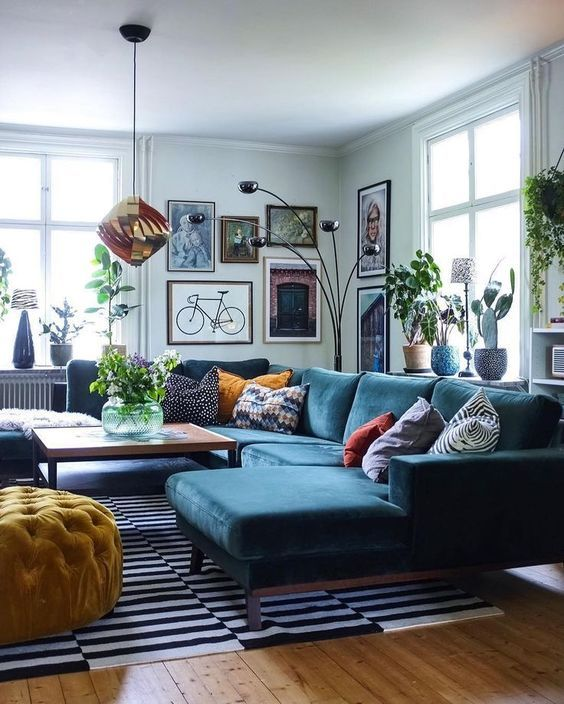 34 a Scandinavian inspired living room with light blue walls, a navy sectional, a bold gallery wall and touches of copper and black