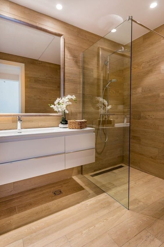 a contemporary bathroom fully clad with wood, with a white floating vanity and built-in lights
