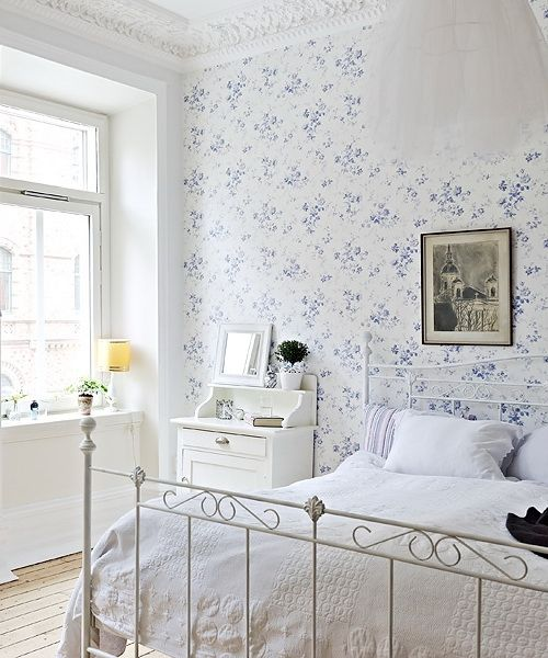 a vintage-inspired bedroom with a blue floral wall, a white forged bed, white furniture, a dark artwork and a pendant lamp