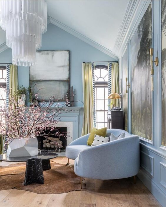a refined living room with light blue walls, exquisite furniture, a statement chandelier and statement artworks