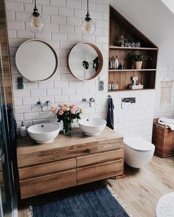 a small and cozy bathroom clad with white subway tiles, a floating vanity and a niche done with wood plus white appliances