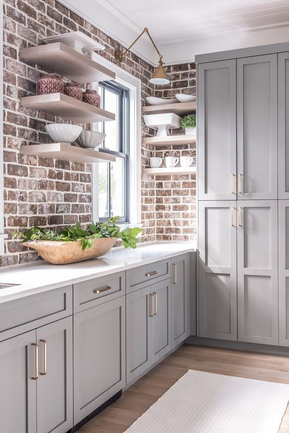 an elegant grey farmhouse kitchen with vintage-inspired cabinets, brick walls and a white stone countertop