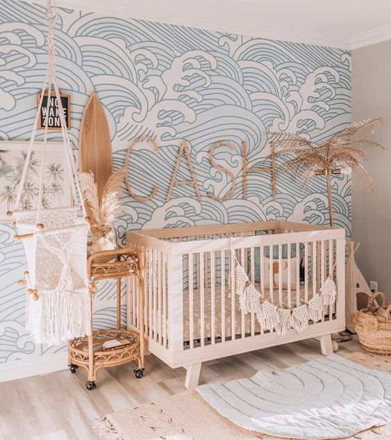 an ocean wave nursery with a bleu wave print wall, neutral furniture, baskets and a rattan cart for storage