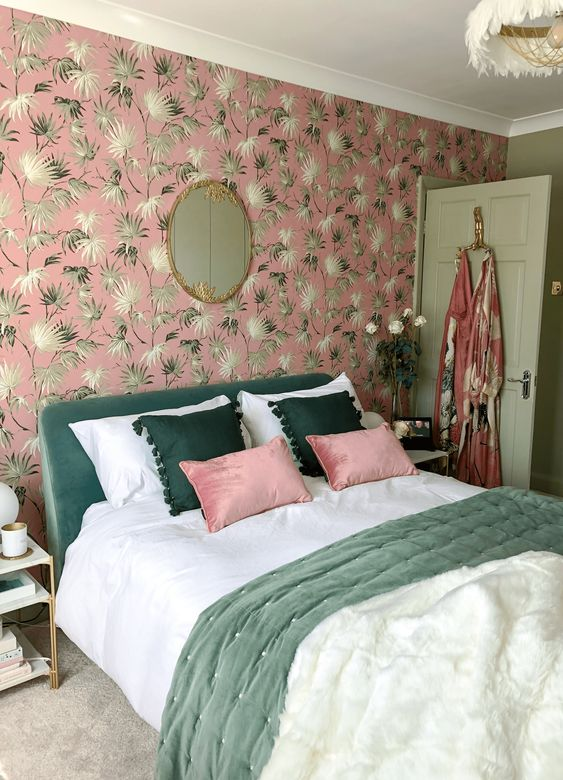a glam and cool bedroom with a pink botanical wall, a green bed, green and pink pillows and a feather chandelier