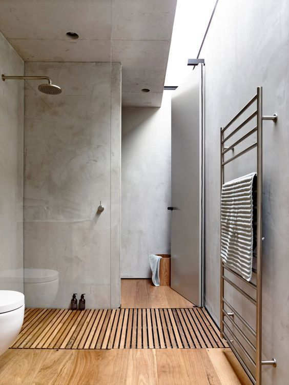 a minimalist bathroom with concrete walls and a skylight, a wooden floor plus neutral appliances
