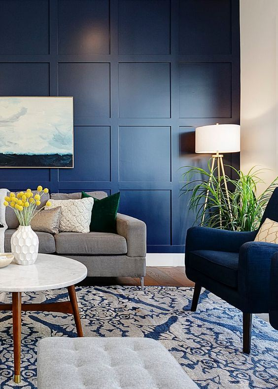 36 a modern living room with a navy panel wall, navy and grey furniture, potted greenery and a sea artwork