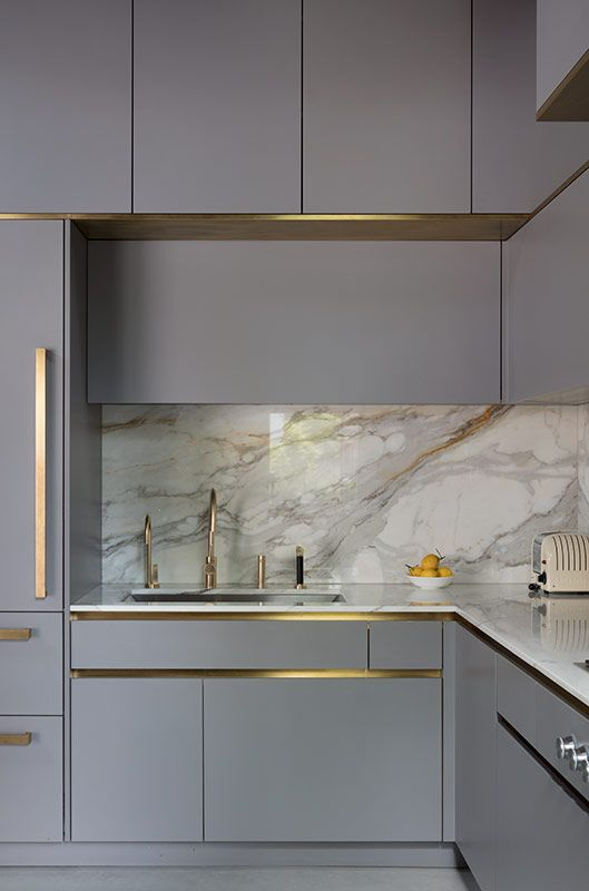 a beautiful grey kitchen with built-in lights, a white marble backsplash and countertops plus gold fixtures