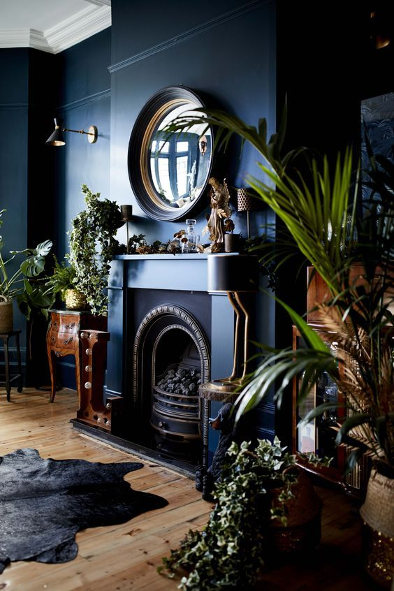 a moody refined living room in navy, with a fireplace, a mirror and heavy wooden furniture plus lots of plant