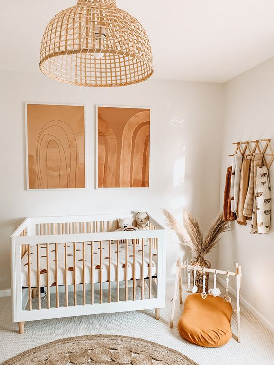 a neutral nursery with rust and orange touches, printed textiles, a rattan pendant lamp and pampas grass