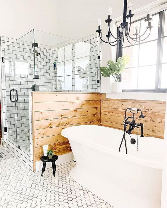 a farmhouse bathroom with white subway and hex tiles, wooden panels, a vintage bathtub and vintage chandeliers