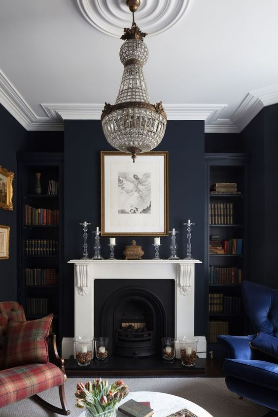 38 a moody living room with midnight blue walls, navy and plaid red furniture, a fireplace, a crystal chandelier and lots of books