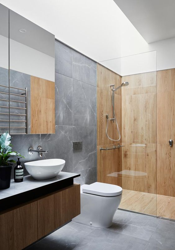 a contemporary bathroom with grey marble tiles and wooden paneling in the shower space, a floating vanity and a skylight
