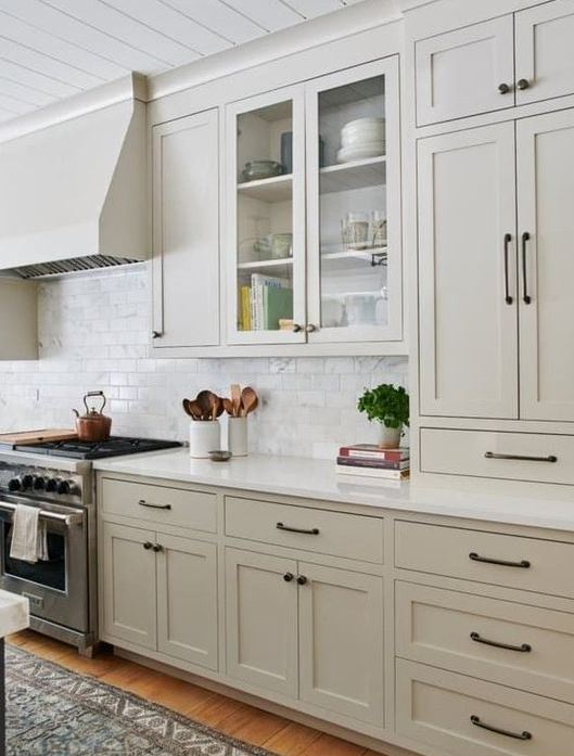 a contemporary greige kitchen with vintage cabinets, black handles and a white marble tile backsplash plus white countertops