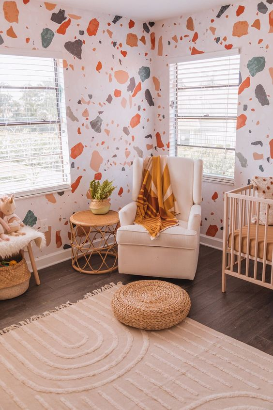 a pretty nursery with terrazzo walls, earthy and light-colored furniture and accessories and potted plants