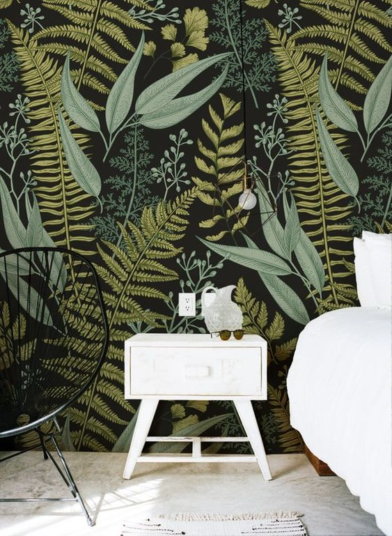 moody botanical print wallpaper is paired with black and white furniture to create a contrast and look outstanding