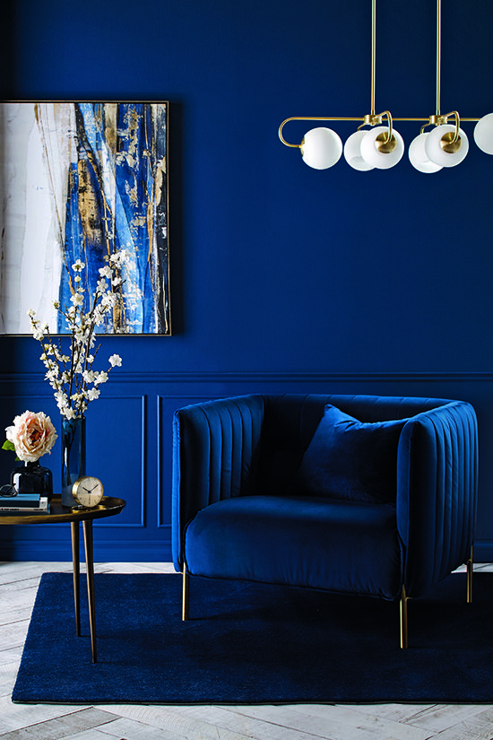 40 a bright living room with bold paneled walls, a bold blue chair, a modern chandelier and a gorgeous artwork