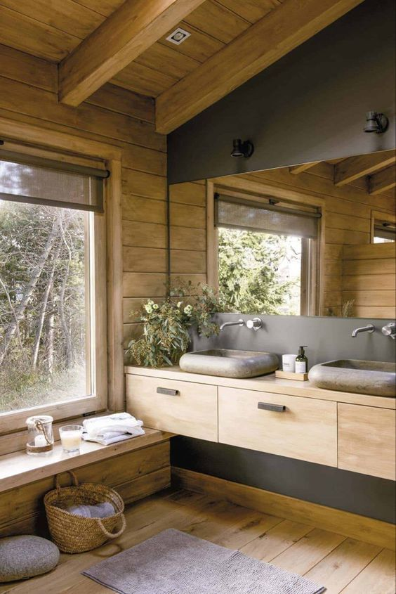 a cabin bathroom of wood and concrete, with stone sinks, a large mirror and a large window for a view