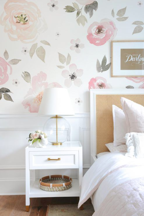 a lovely bedroom with a watercolor floral wall, a bed with a rattan headboard, white nightstands, gold touches