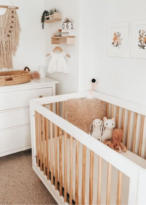 a neutral and earthy tone nursery with a macrame hanging, modern furniture, a gallery wall and pretty toys
