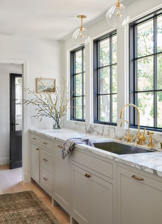 a refined greige kitchen with a white marble countertop and gold fixtures and a faucet is a stylish idea