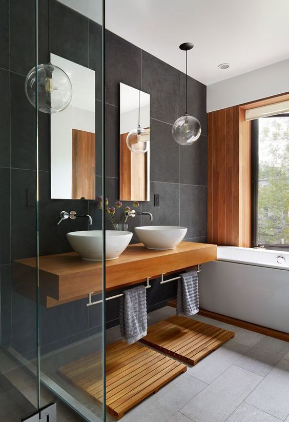 a contemporary bathroom with large scale dark grey tiles, a wooden accent wall, a floating vanity and mats