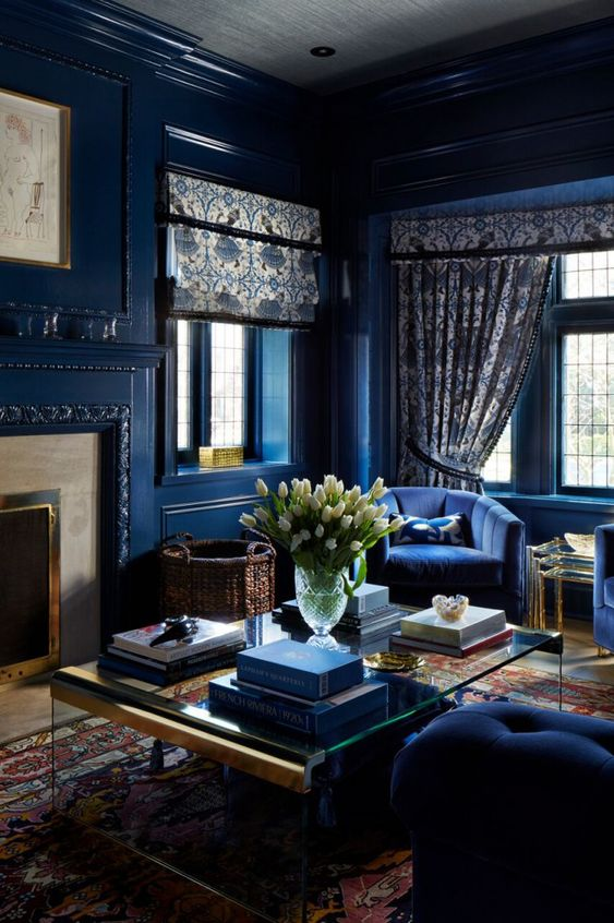 a monochromatic refined navy living room with a fireplace, chic navy furniture, printed textiles and baskets