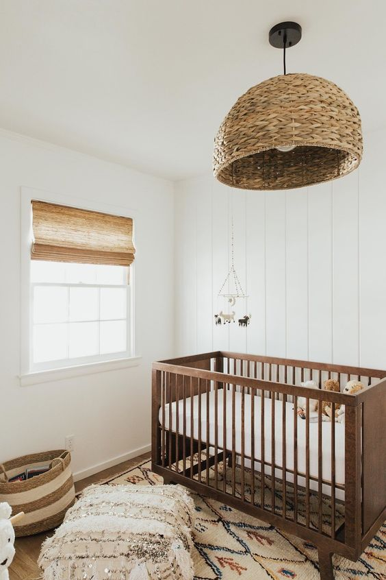 a neutral rustic nursery done with earthy tones and a rattan lamp, a stained crib and printed textiles