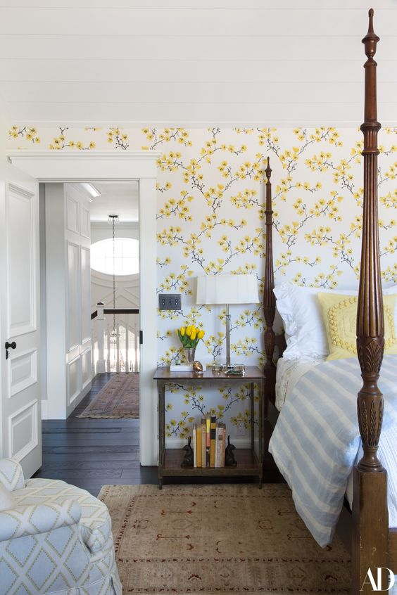 a vintage-inspired bedroom with yellow floral walls, a heavy bed with pillars, a chair and nightstands plus blooms