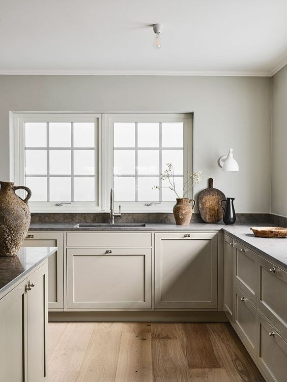 a warm and welcoming greige Scandinavian kitchen with vintage cabients and walls matching in color, dark countertops and a tiny backsplash