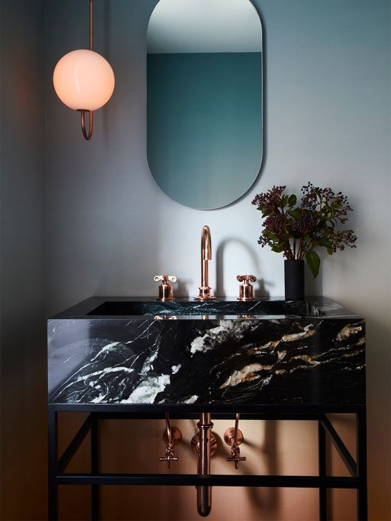 a catchy and refined bathroom in blue and orange, with a black marble vanity and copper fixtures is chic