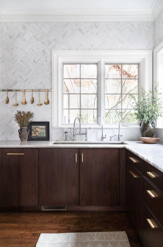 a jaw-dropping walnut kitchen with white stone countertops and white marble tiles plus touches of gold
