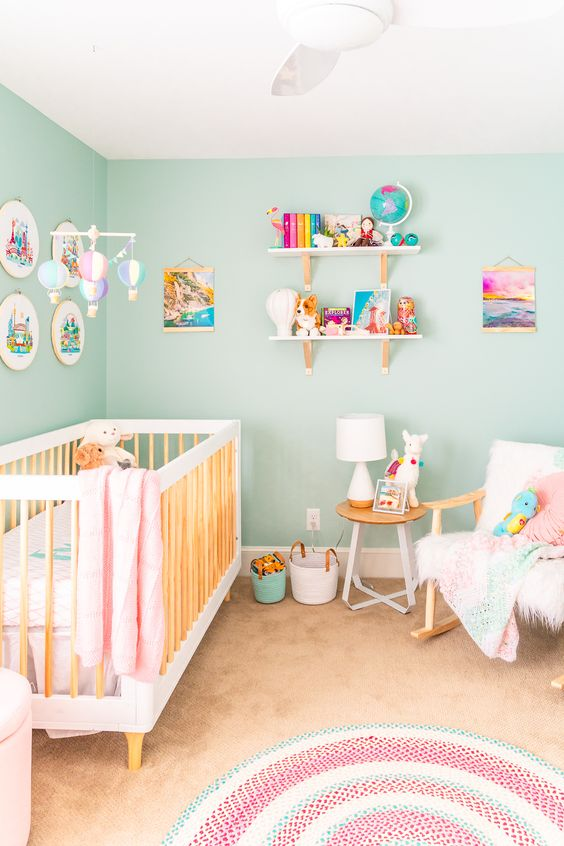 a pastel travel-themed nursery with turquoise walls, pink and mint touches and bright artworks