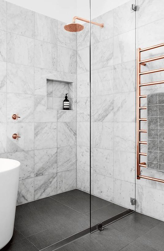 a chic bathroom with white marble tiles and a grey tile floor, copper fixtures for a softer and more refined touch
