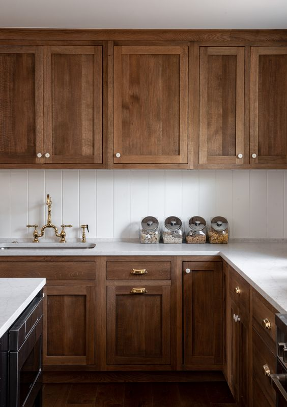a classic walnut kitchen with vintage cabinetry, gold fixtures, a white tile backsplash and white stone countertops