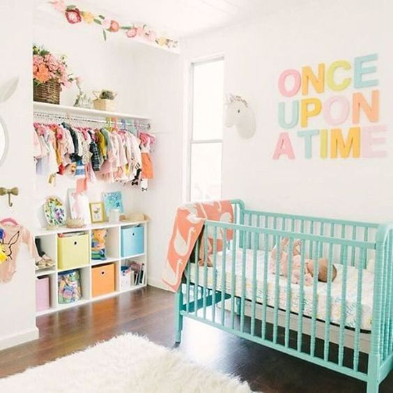 a neutral nursery with a turquoise crib and a pretty pastel letter artwork plus colorful clothes and boxes