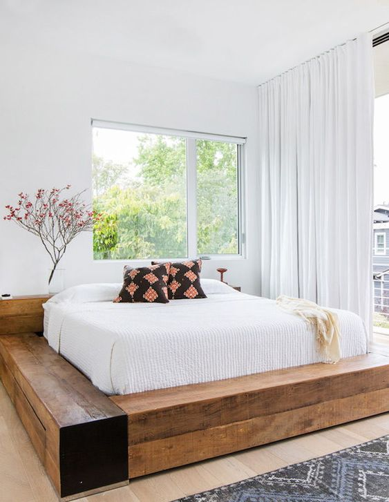 an airy bedroom with a bed made of wooden slab is a welcoming space with a strong rustic feel