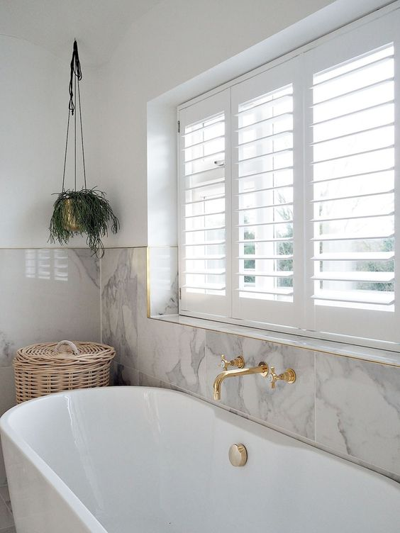 44 a chic and refined bathroom with grey marble tiles, a chic tub and gold fixtures plus potted greenery