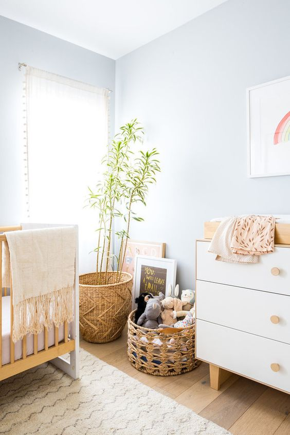 a pastel blue nursery with neutral furniture, baskets and potted greenery plus bright artworks