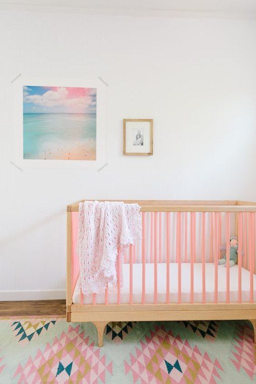 a pastel nursery with a pink crib, a bright pastel rug and a bold artwork is a pretty space to be
