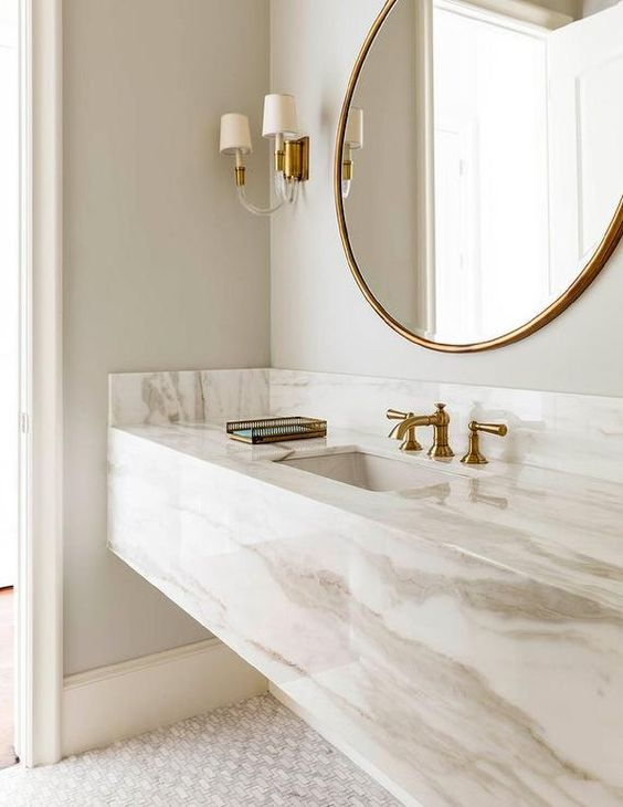 a refined neutral bathroom with a white marble slab vanity plus brass touches for a more exquisite look