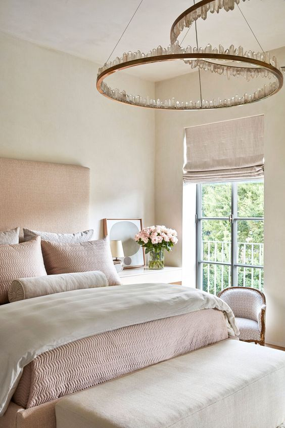 a soft and lovely bedroom with a pink upholstered bed, crystal chandeliers, pink and creamy bedding