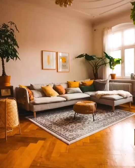a modern warm toned living room with blush walls, a grey sectional, mustard and yellow pillows and potted plants