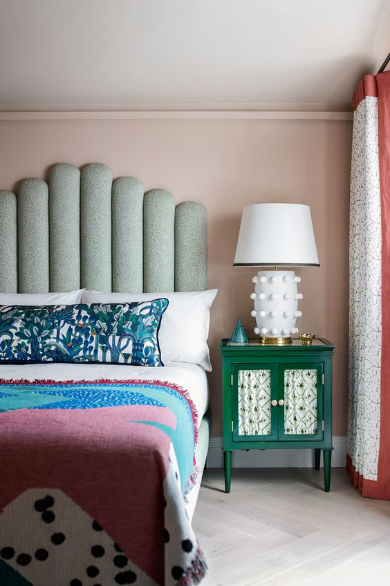 a pastel bedroom with a statement bed with a green statement headboard, bright bedding and textiles