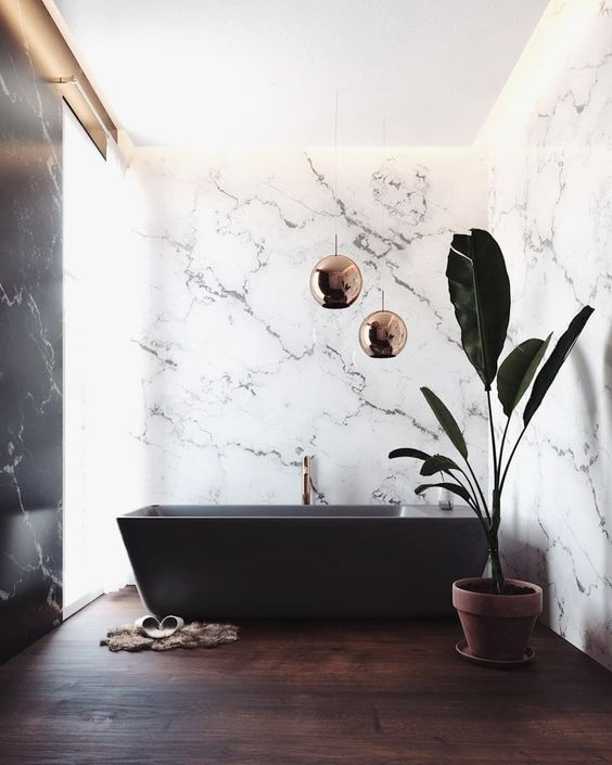 a sophisticated bathroom with white marble walls, a dark stained floor and a black bathtub and copper lamps