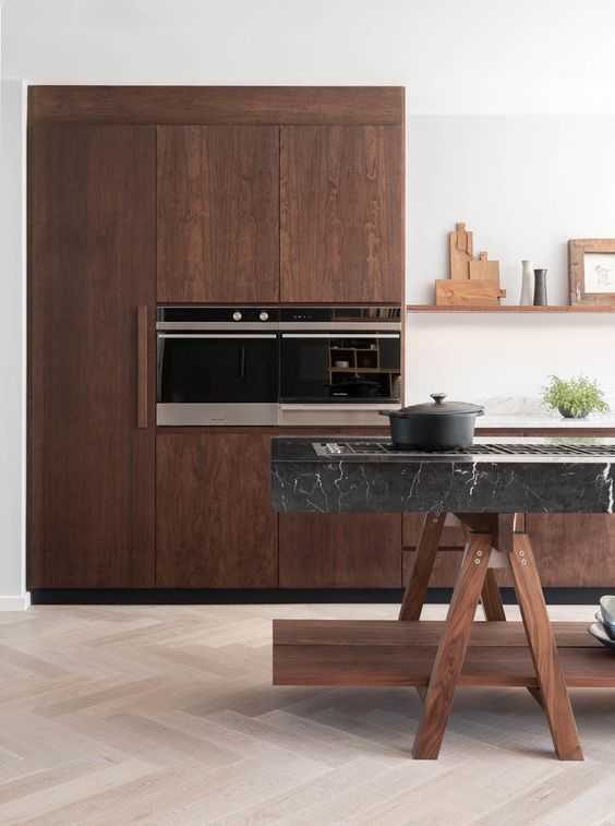 a stunning walnut kitchen with a unique trestle kitchen island topped with black marble looks just amazing