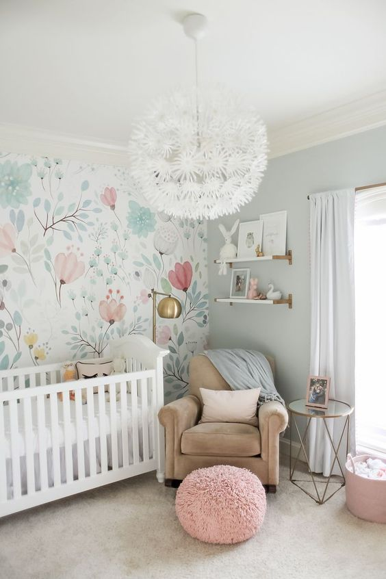 a whimsical pastel nursery with a floral accent wall, blue walls, touches of blush and pink and a floral chandelier