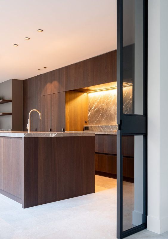 a minimalist walnut kitchen with sleek cabinetry, a grey marble backsplash and countertops and gold fixtures