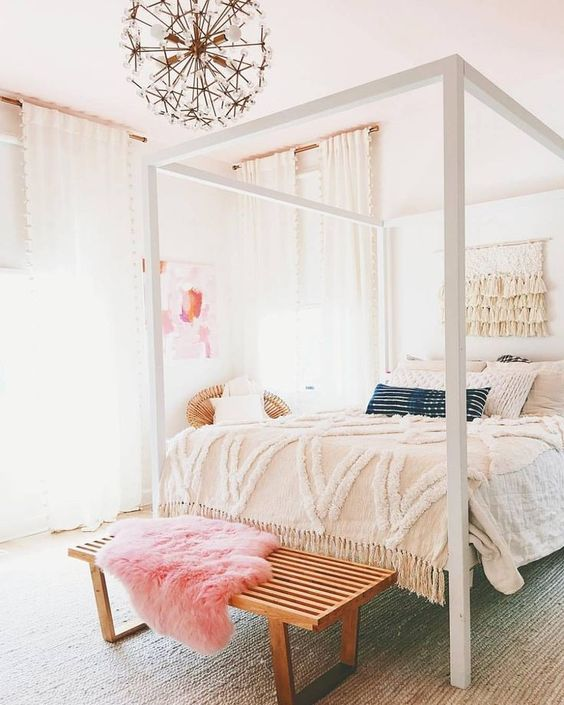 a neutral bedroom with a statement canopy bed, a bench with a pink throw, a lovely floral chandelier